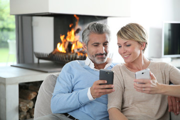 Middle-aged couple using smartphone at home by fireplace