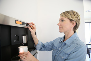Middle-aged woman using expresso coffee machine