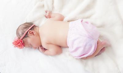 sweet newborn sleeping on a blanket