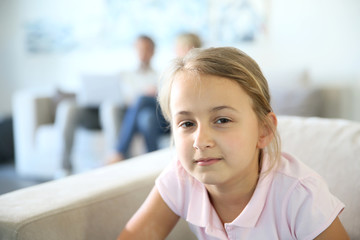 Portrait of 8-year-old girl sitting in sofa