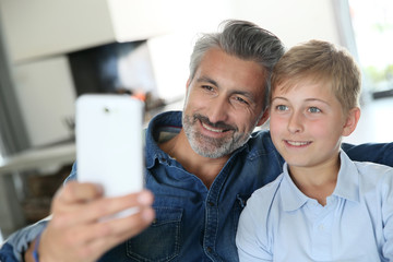 Father and son taking picture of themselves with smartphone