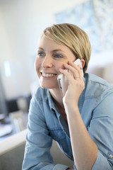 Middle-aged blond woman talking on phone at home