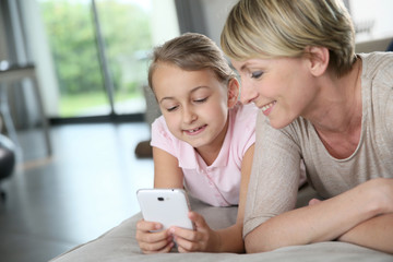 Mother and young girl playing with smartphone at home