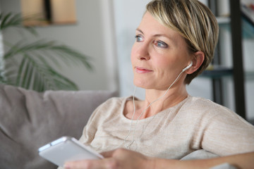 Woman relaxing in sofa using smartphone and earphones