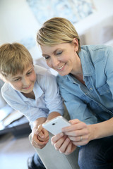 Mother and pre-teen using smartphone at home
