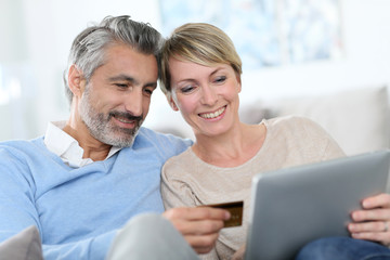 Cheerful mature couple e-shopping on internet