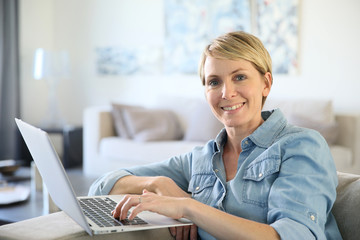 Middle-aged woman sitting in sofa and using laptop