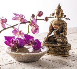 Buddha for zen attitude with stone and flowers