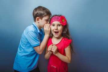 Teen boy whispering in the ear of teen girl on  a gray  backgrou