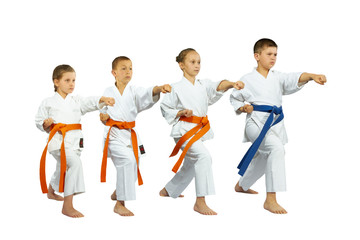 Two boys and two girls in karate position make punch