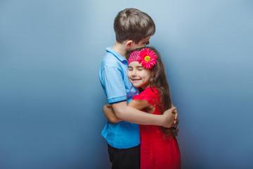 teen girl hugging a teenage boy on gray background