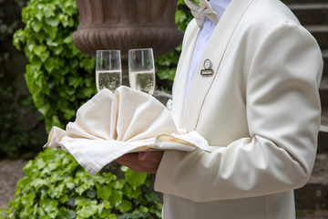 Maitre in giacca bianca con vassoio e due bicchieri di champagne