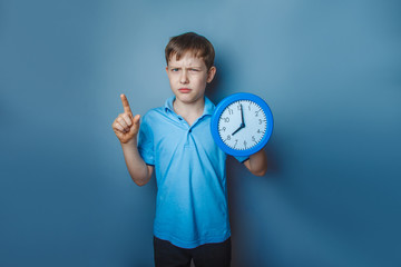 Boy teenager European appearance ten years holding a wall clock