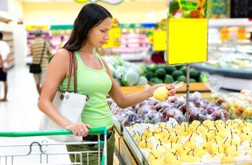 woman buys pear in the supermarket
