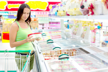 Woman buying ice-cream at the supermarket