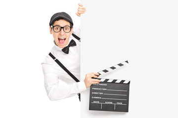 Movie director holding clapperboard behind a panel