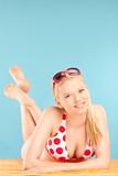 Beautiful young woman in bikini lying on a beach