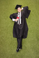 Pensive graduate holding diploma and lying in a field