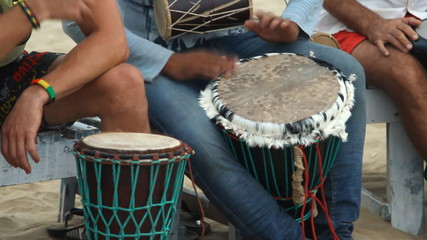 Unidentified man playing on drum at the beach