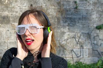 Girl listening to music wearing big sunglasses