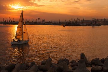 Sailing yacht enters Varna harbor at the sunset