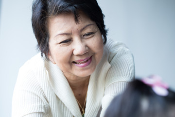 Asian young golden age woman smile happy with granddaughter