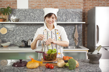 an Asian girl cooking salad in the kitchen with chopstick