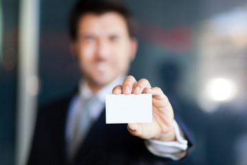 Defocused businessman showing an empty business card