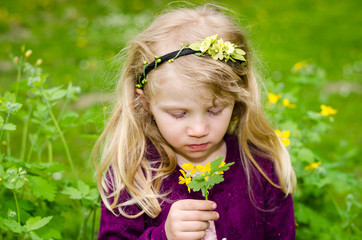 beautiful blond girl smelling flowers