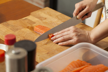 an Asian woman chef preparing salmon piece with sharp knife