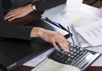 business concept - businesswoman working with calculator in