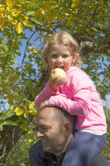 Man with little girl sitting on his shoulders eating an apple