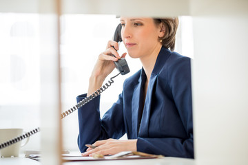 Businesswoman at her Desk Answering a Phone Call