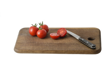 Juicy organic Cherry tomatoes on cutting board isolated on white