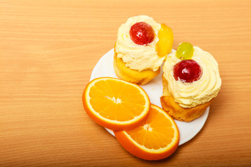 Gourmet cream cake cookie and orange on plate