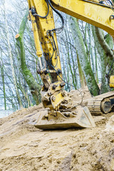 Excavator digging on site in forest environment.