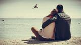 Fototapety couple sitting on beach rear view