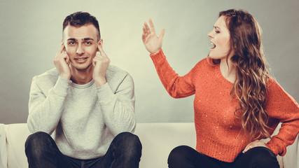 Angry fury woman screaming man closes his ears.