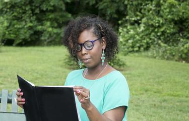 Beautiful African American woman reading a  book in park