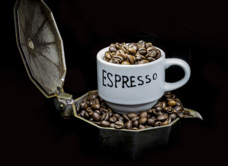 Espresso cup on coffeepot with coffee beans