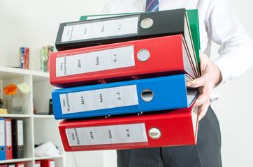 Businessman holding a pile of binder
