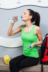 Girl in locker room drinking water after fitness training