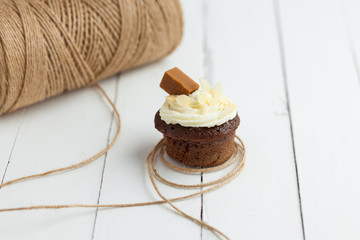 Fresh chocolate cupcake with iris and almonds on wooden table