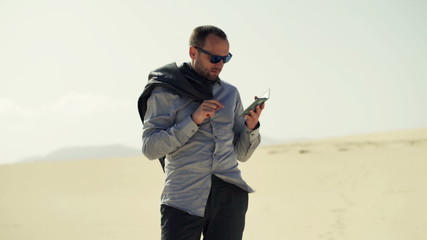 Lost businessman checking map on smartphone on desert