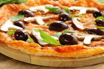 Italian pizza with olives and mushrooms on a wooden board