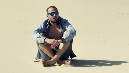 Young man relaxing while sitting on desert