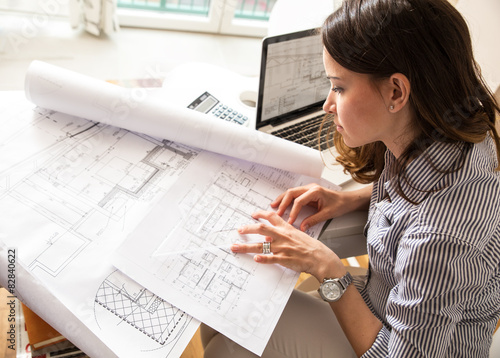 Female architect working at home.She looking at blueprint. Poster
