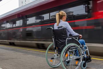 Frau sitzt in einem Rollstuhl auf einem Bahnhof