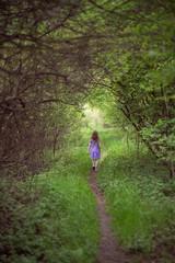 Little lonel girl in green nature gateway