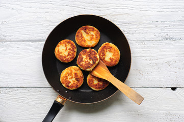 Cottage cheese pancakes in frying pan on wooden background